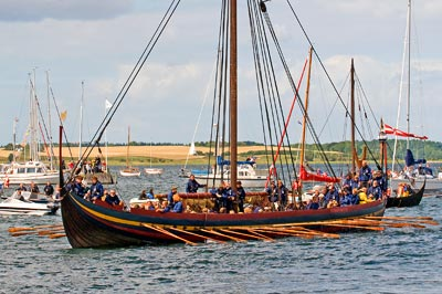 Viking ship with the oars out rowing into a harbor